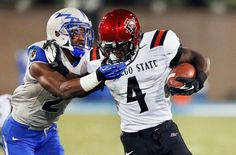 Air Force defensive back Christian Spears tackles San Diego State running back Adam Muema