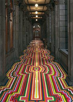 Trabalhos do artista escocês Jim Lambie dão vida a ambientes sóbrios com tiras coloridas, posicionadas de maneiras que sugerem até ilusões de ótica