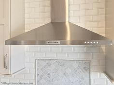 KitchenAid Stainless chimney-style #hood and #Carrara Marble with #beveled subway tile. | VillageHomeStores.com