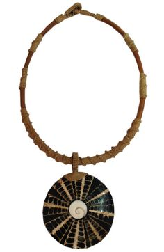 A distinctive wooden choker necklace with cone shell pendant and a shiva eye inlay.