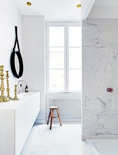 Carrara marble elevates any bathroom, whether used in small or large quantities. Here, marble floors and walls dominate the space, which is accented with a red shower fixture, leather hanging...