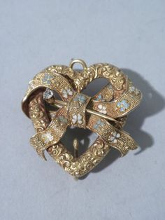 Executed in 14K gold, this very pretty Edwardian-style pin is in the shape of a heart tied with a bow. The heart has wonderful scroll decoration while the furling ribbon bow that wraps around it has a textured matte background with delicate pale blue and white enameled flowers. Tucked in the ribbon is a gold stickpin-style piece topped with a circular, cut diamond. This lovely pin is a charming example of American jewelry design from the period around 1900. For more information, click here.