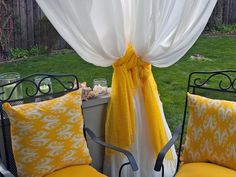 DIY Outdoor Projects Inspired by Boutique Hotels : Fashion a Craft your own private cabana by hanging white cotton sheers around your deck or balcony. Give it resort-style flair by tying them back with sunny yellow scarves.