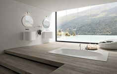 This bathroom design is white, simple, and clean, and inviting. Nothing distracts from this bathtub with a view.
