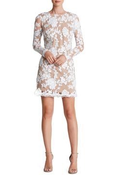 Glittering sequined blooms sprawl across this romantic lace cocktail dress styled with sheer full-length sleeves and gently scalloped edges.