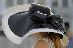 Carrie Cooke, Louisville, Ky., wears a fancy hat while walking through the paddock before the 138th Kentucky Derby horse race at Churchill Downs Saturday, May 5, 2012, in Louisville, Ky