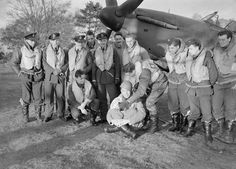 Squadron Leader Robert Stanford Tuck (centre) with pilots of No. 257 Squadron RAF under the nose of Tuck's Hawker Hurricane at Martlesham Heath. They are displaying souvenirs of their action against Italian aircraft on 11 November Battle Of Britain Movie, Hawker Hurricane, Flying Ace, Great Yarmouth, Ww2 Pictures, This Is Your Life, Ww2 Planes, Fighter Pilot, Ww2 Aircraft