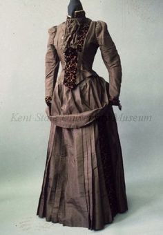 1885 Day Dress Culture: American Medium: silk taffeta, velvet, satin Brown silk taffeta and brown velvet flowers cut to rust satin day dress. Long waisted bodice with standing collar of cut velvet, velvet lapel on left and inset at waist, dickie of gathered silk with buttons on right, sleeve with puffed shoulder and fitted lower arm with velvet cuff. The skirt with pleated front and velvet inset on left side, overskirt draped over hip.
