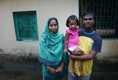 Iqbal Hussein, a union leader with the Bangladesh Poshak Sromik Trade Union, stands outside his home with his wife Soma Begum and 2-year-old daughter, Aini  Read more: http://www.post-gazette.com/gallery/Bangladesh-slideshow-by-Julia-Rendleman#ixzz3CKNieOIO  Photo credit: Julia Rendleman/Post-Gazette