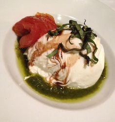 Giao burrata in a basil pesto bath, drizzled with balsamic and roasted tomato