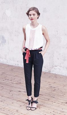 white blouse with pleated front tucked into black cigarette trousers, tied at to show floral pattern underneath. ribbon-tied heels, deep pink lips and halo twist