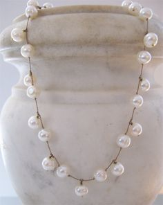 white pearls on tan silk cord.  I could totally make this!