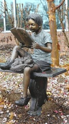 """Statue of a child enjoying a book on a bench is one of the focal points of the Roenna Fahrney Garden outside the Bel Air branch of the Harford County Public Library.  The piece of art is called """"Marley and Me,"""" from The Randolph Rose Collection in Yonkers, N.Y., and cost the library system about $5,800."""