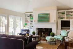 Beautiful living room features a green striped art piece leaning against a paneled fireplace wall over white mantle accented with glossy black surround flanked by built-ins fitted with a TV cabinet housing flatscreen hidden behind folding doors. Desk In Living Room, Home And Living, Living Spaces, Monochromatic Living Room, Fireplace Bookshelves, Fireplace Wall, Bookcases, White Built Ins, White Mantle