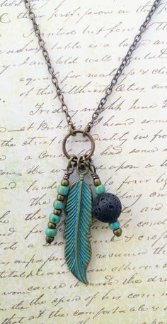 A lovely boho necklace! Use as a diffuser necklace by adding essential oil to the lava bead, or layer with shorter necklaces for a natural, earthy summer look. 30 inch long chain, and the ring and pendants drop 3 inches. See Kids At Heart Bead Shop on etsy for more essential oil necklaces.