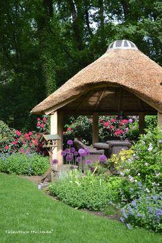 Bostuin met grote vijver en rietgedekt prieel