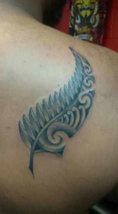 New Zealand Maori Tribal Fern. Love the 'concept', not so much the design or placement though.  I want to get something like this done, but more delicate and as part of an arm-band on my right arm (one feather and one fern hanging down off a simple Celtic band with my tribes' actual patterns on one half of each.  There will be other symbols on there from other cultures too. This entire band will signify the warrior spirit from the tribes/cultures that make up my ancestry (nine in total!!).