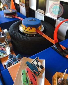 Hot wheels themed tablescape with flag backdrop two fondant covered cakes with cream cheese filling with a track passing thru the cake cake pops mini cupcakes and sugar cookies for a birthday party Hot Wheels Party, Bolo Hot Wheels, Hot Wheels Cake, Festa Hot Wheels, Hot Wheels Birthday, Race Car Birthday, Race Car Party, Cars Birthday Parties, Hotwheels Birthday Cake