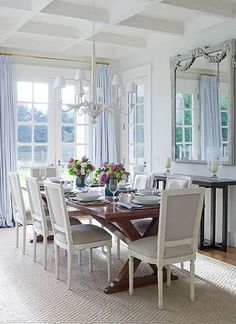 "Light and airy, yet totally elegant dining area in an East Hampton home by Meg Braff. Love the calming whites and greys of the walls and mouldings, the Stark ""Neptune"" carpet, the upholstered chairs, the antique mirror, the eight-armed chandelier contrasting with the powdering blue drapes and the view of the green garden through the french doors."