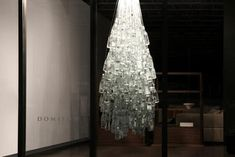 """Paprika Design Studio has created an unconventional Christmas tree for Montreal-based furniture retailer Domison. Known as the """"Ice-Tree,"""" the tree is being showcased in Domison's store in Montreal. The tree is made from more than 300 Canadian mineral glass water bottles assembled together. The tree was made by four people after two days of intensive glasswork. Since the tree makes use of recycled glass, light falling on the artwork is reflected back, creating an ice-like sparkle."""