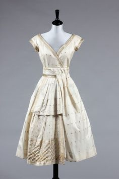 A sari silk cocktail dress, similar to the Dior 'Delphine' model, A/W 1956, with cross-over bodice with sash to skirt.