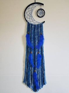 This beautiful Dream Catcher is completely hand made. Its made with a 10 inch wooden hoop cut to size, and hand wrapped with deep navy and blue yarn. It has multicolored blue and white yarn hanging with blue feathers, that is roughly 2 foot in length. The star is made to match