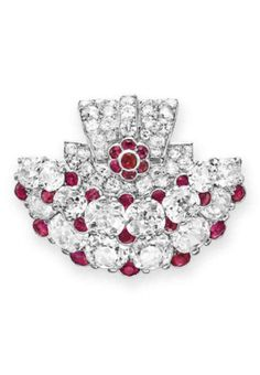 AN ART DECO DIAMOND AND RUBY CLIP BROOCH, BY CARTIER  Designed as an old mine-cut and circular-cut diamond plaque, enhanced by collet-set ruby detail, mounted in platinum, circa 1925 Signed Cartier, Paris, no. L2?21