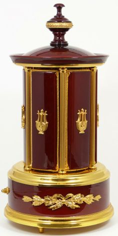 """Reuge Swiss music box ciigarette disppenser. Has a red enamel finish  with gold mounted lyres and ribbons. Interior has a spinning ballerina. Plays the song """"Le Bleu Danube"""""""