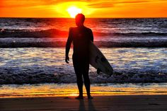 Surfer watches the sunset in Oceanside.