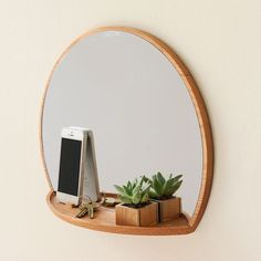 """Rise & Shine Mirror by Lu LiuLiu's hanging mirror with a built-in storage shelf is inspired by the circle of life. """"The outline of the mirror looks like the rising sun,"""" the designer says."""