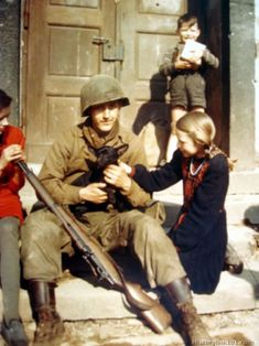 An infantryman makes friends with a dog belonging to German children.