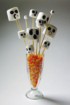 """Perfect Halloween centerpiece: This spooky """"bouquet"""" featuring ghost marshmallows in candy corn!"""