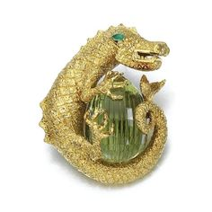 Gold, peridot and emerald brooch, David Webb. Designed as a dragon clutching a multifaceted peridot egg, with an emerald eye, mounted in yellow gold, can be worn as a pendant, signed Webb. weight 115.