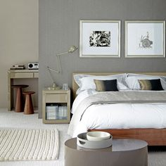 Clever idea; this sophisticated grey bedroom has a floating wall which has been created in front of the original wall and decorated with two different shades and textures. Positioning the bed against the new wall and fitting shelves and rails behind it creates a dressing area with hidden storage - the perfect contemporary alternative to wardrobes.