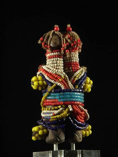 Africa | Fertility Doll ~ ham pilu  ~ from the Fali  people of Cameroon | Wood, leather, glass beads, cotton | When a young Fali man becomes betrothed, he makes a ham pilu and gives it to his fiancee, who wears it in a baby carrier on her back. The doll is a symbol of their marriage commitment and represents their future child. The man gives the doll the gender that he desires for his first-born. The woman cares for the figure until the child is born; then the doll is carefully stored away.