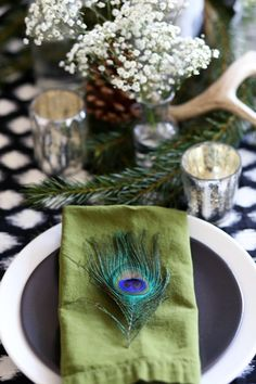Peacock feathers placed on top of tables with babies breath flowers.  Great table place settings.