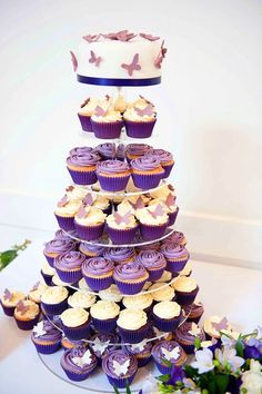 Violet wedding cake and cupcake tower with butterflies