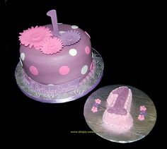I like the idea of giving a smash cake in the shape of 1. (Purple and pink first birthday cake daisies and polka dots by Simply Sweets)