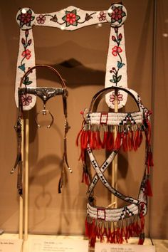 Bridles. Red fringe is a Lakota bridle (ca. 1895) from South Dakota or North Dakota. Floral pattern on white background is a Cree bridle (ca. 1900) from Canada. Silver headstall is Dine (Navajo) by John Silver (ca. 1970) from New Mexico (the 'e' in Dine is accented).  Most often Native Americans simply inserted rope into the horse's mouth in the gap between the teeth, then looped and tied the rope around the horse's head and formed a single rein.