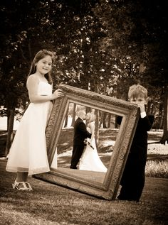 Have your ring bearer and flower girl hold a frame with the new bride and groom posing behind it!