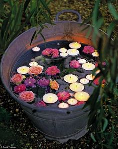 Floating flowers and candles at night in containers. www.ContainerWaterGardens.net