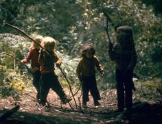 Four children from a hippie commune walking through the woods with their sticks. Photograph by John Olson. Sunny Valley, Oregon, USA, 1969.