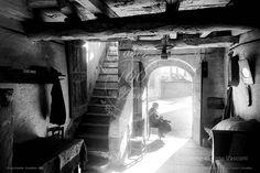 """Piazza castello – Cernobbio – Lago di Como - 1929  Interno di una tipica abitazione del centro storico di Cernobbio dei primi del '900,  animata in controluce da una donna sull'uscio di casa intenta a cucire. Il negativo fotografico originale impresso su lastra di vetro  fà parte dell'Archivio storico fotografico Vasconi di Cernobbio, ed è stato riprodotto in formato digitale, restaurato dalle impurità del tempo, dallo studio fotografico """" i Vasconi"""" di Piero Vasconi."""