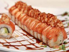 Por dentro queso crema, pepino y aguacate, por fuera rodeado de salmón con topping de camarón spicy bañado en salsa de anguila