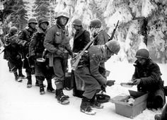 The issuance of dry rations to the the 347th Infantry Regiment of the 87th Infantry Division on the way to La Roche, Belgium (January 13, 1945). Note the soldiers' mess kits, the early-style M1 carbine, and a grenade on the collar of the soldier handing out the food. Via the National Archives, by Newhouse (Image 111-SC-198849)