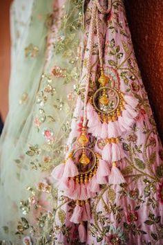Pretty tassel latkan on pink bridal lehenga. See more on wedmegood.com #wedmegood #indianwedding #indianbride #tassel #bridallehenga #lehenga #lehengacholi #pink #pinklehenga