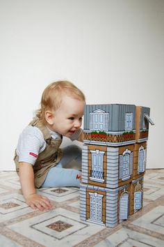 Cardboard blocks as small buildings, stackable to create a city, and with flaps on windows & doors that open to reveal a surprise. (Cat on window-sill, car in garage, etc.)