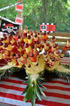 Pirates fruit kabobs, displayed in pineapples. Must eat plenty of fresh fruit and vegetables to avoid scurvy. These kabobs are simple and delicious. Pirate's Nightmare in the Caribbean Halloween Party Decorations & Menu Ideas.