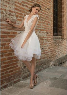 Ivory short wedding dress crafted in tulle, satin and lace. A-line knee-length dress with deep V neckline and open back