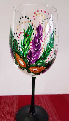 Mardi Gras - Wine Glass- Hand Painted - Masquerade masks- 19oz Wine Glass- Green/ Purple/ Gold Design (ONE GLASS). This glass features one of my 10 Masquerade mask designs. A Perfect party glass for any celebration. They also make a great Birthday, Christmas, Holiday or Just Because Gift!!  These glasses have been baked at high temperatures to ensure dishwasher resistance.  Also sold individually so you can feel free to mix and match if you would like. See other listings for more designs to…